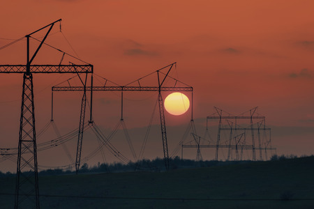 Industrial landscape with high-voltage power line, electric tower and rising sun