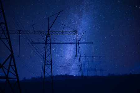 Industrial night landscape with high-voltage power line, electric tower and stars an sky