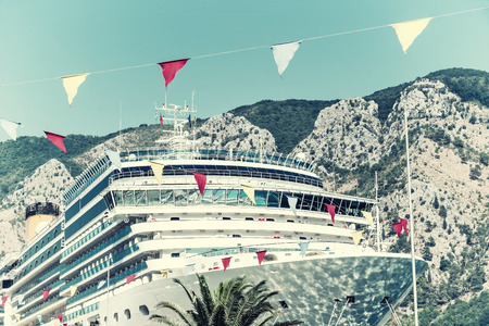 Big liner in port on mountains background. Travel and vacation, Montenegro. Vintage stylization, retro film filter Imagens