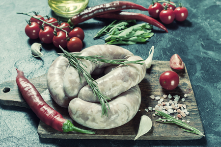 Raw chicken sausages with chili and tomatoes on cutting board, black culinary background, selective focus. Vintage stylization, retro film filter