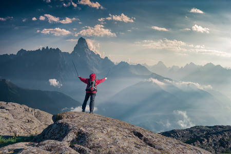 Mountaineer with backpack on rock enjoying view of big mountains, hiking lifestyle, man on top.
