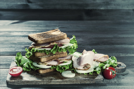 Sandwiches with sausage and vegetables on dark wooden table. Vintage stylization, retro film filter