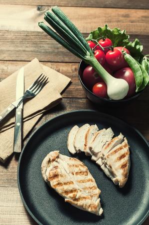 Grilled chiken fillet on frying pan. Raw vegetables in bowl, wooden background. Vintage stylization, retro film filter