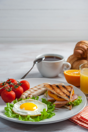 Fried eggs with sausages and vegetables on plate. Breakfast with orange juise and croissant on wooden rustic boards, food background. Banque d'images