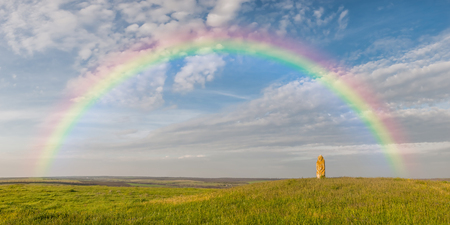Landscape with rainbow over summer wild steppe. Polovtsian idol on hill, beautiful sky Imagens
