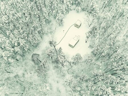 Winter landscape with house in forest. Trees covered by snow, aerial view. Vintage stylization, retro film filter