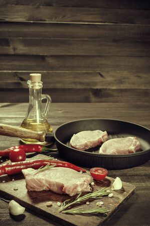 Pieces of raw pork on cutting board, ready to roast. Spices and oil, kitchen background. Retro stylization, vintage film filter Stock fotó