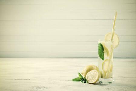 Homemade lemonade with mint from lemone and orange, citrus refreshig beverage in glass. Retro stylization, vintage film filter