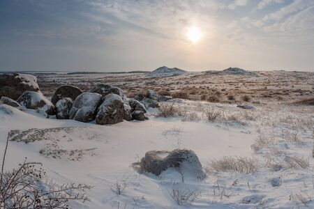 Winter landscape with hills covered snow. Icy grass in snowy prairie