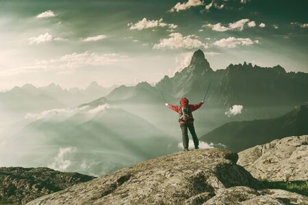 Mountaineer with backpack on rock enjoying view of big mountains, hiking lifestyle, man on top. Vintage stylization, retro film filter