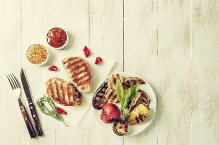 Fried pork fillet and grilled vegetables, delicious barbecue dinner, flat lay food background. Vintage stylization, retro film filter 版權商用圖片