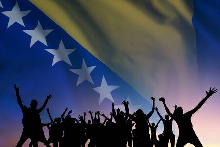 Silhouette di popoli sulla bandiera e sullo sfondo del cielo, giorno della Bosnia-Erzegovina, festa dell'indipendenza