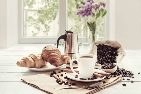 Breakfast with aromatic black coffee and croissant, good morning, great start to the day. Coffee break, copy space. Vintage stylization, retro film filter