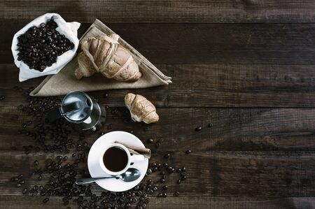 Breakfast with aromatic black coffee and croissant, good morning, great start to the day. Coffee break, copy space, flat lay. Vintage stylization, retro film filter