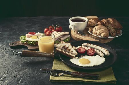 Fried sausage with eggs and vegetables on pan. Delicious breakfast with orange juise and croissant on wooden rustic boards, food background. Vintage stylization, retro film filter