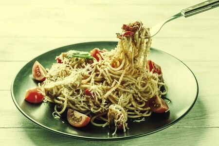 Italian spaghetti pasta with sauce and chicken, cheese parmesan and basil. Food background, flat lay. Vintage stylization, retro film filter