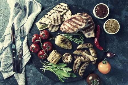 Fried pork fillet and grilled vegetables, delicious barbecue dinner, flat lay food background. Vintage stylization, retro film filter Фото со стока