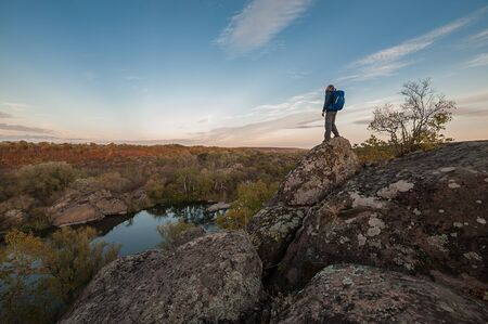 Hiker with backpack on edge of canyon, hiking lifestyle, man on top. Autumn landscape