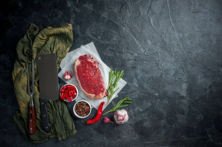 Beef steaks rib eye ready to cooking, culinary background. Fresh raw meat on wooden cutting board with rosemary, flat lay