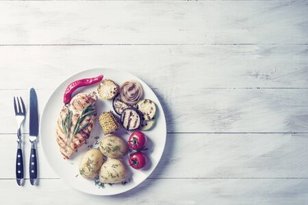 Fried chicken fillet and grilled vegetables, delicious barbecue dinner, flat lay food background. Vintage stylization, retro film filterVintage stylization, retro film filter