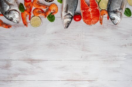 Fresh dorado, seabass, salmon fishes and shrimps on bord prepared to cooking, vegetables and fresh sea food. Cooking background, flat lay