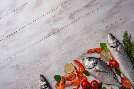 Fresh dorado, seabass fishes and shrimps on bord prepared to cooking, vegetables and fresh sea food. Cooking background, flat lay Фото со стока