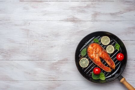 Fried salmon fishes in pan, cooking delicious and healthy, fresh sea food. Cooking background, flat lay Фото со стока