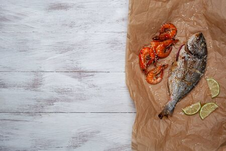 Fried dorado fishes and shrimps on paper, cooking delicious and healthy, fresh sea food. Cooking background, flat lay
