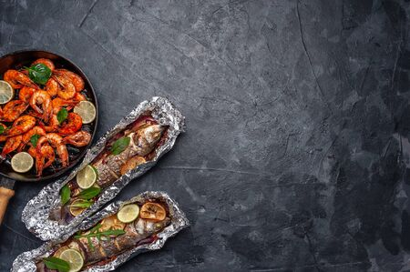 Fried seabass fishes and shrimps in pan, cooking delicious and healthy, fresh sea food. Cooking background, flat lay