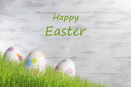 Easter colorful eggs on wooden backdrop, holiday background for your decoration. Egg hunt, copy space, Happy Easter lettering Фото со стока