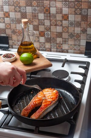 Fried salmon fishes in pan on cooker, cooking delicious and healthy, fresh sea food. Cooking background Фото со стока