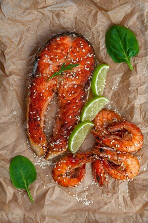 Fried salmon fishes and shrimps on paper, cooking delicious and healthy, fresh sea food. Cooking background, flat lay Фото со стока