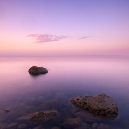 Summer landscape with calm water on sea, cloud in beautiful sky. Minimalistic view, long exposure Фото со стока