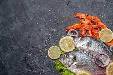 Fresh dorado fishes and shrimps on bord prepared to cooking, vegetables and fresh sea food. Cooking background, flat lay