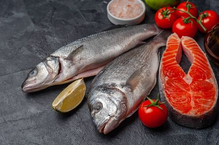 Fresh dorado, seabass, salmon fishes and shrimps on bord prepared to cooking, vegetables and fresh sea food. Cooking background, selective focus Фото со стока