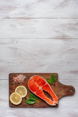 Fresh salmon fishes and lemon on bord prepared to cooking, vegetables and fresh sea food. Cooking background, flat lay
