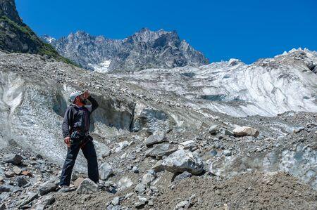 Mountaineer on rock enjoying view of big mountains, hiking lifestyle, man on top. Travel adventure on highland