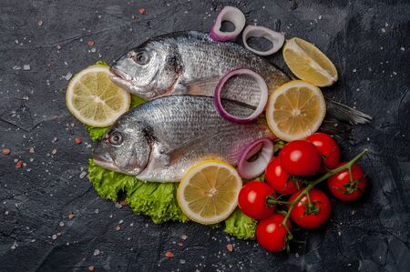 Fresh dorado fishes on bord prepared to cooking, vegetables and fresh sea food. Cooking background, flat lay Фото со стока