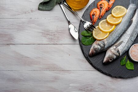 Fresh seabass fishes and shrimps on bord prepared to cooking, vegetables and fresh sea food. Cooking background, flat lay