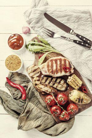 Fried pork fillet and grilled vegetables, delicious barbecue dinner, flat lay food backgroundÑŽ Vintage stylization, retro film filter