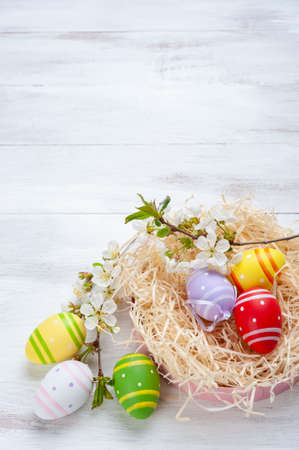 Happy easter painted eggs with flowers on wooden colorful table, holiday background