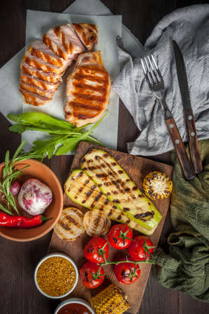 Fried pork fillet and grilled vegetables, delicious barbecue dinner, flat lay food background