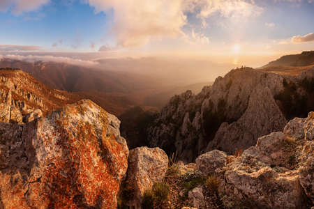 Beautiful sunrise on autumn landscape with mountains and majestic sky Фото со стока