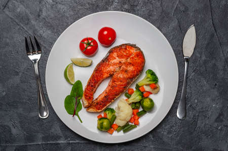 Fried salmon fishes and vegetables on plate, cooking delicious and healthy, fresh sea food. Cooking background, flat lay
