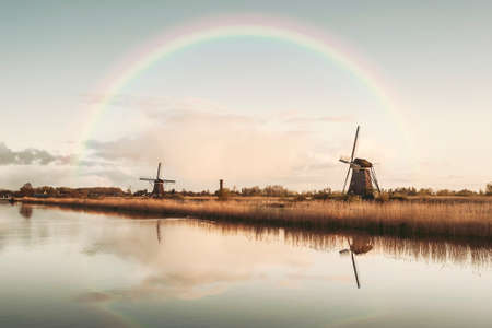 Beautiful landscape with windmills, rainbow and majestic sky reflection in water. Vintage stylization, retro film filter Фото со стока