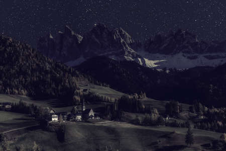 Rural landscape with church in famous village Santa Maddalena and Dolomites mountain peaks at night with stars and moon light. Vintage stylization, retro film filter