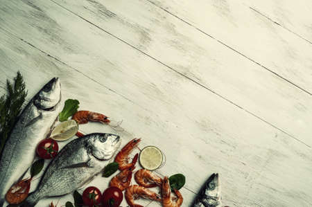 Fresh dorado, seabass fishes and shrimps on bord prepared to cooking, vegetables and fresh sea food. Cooking background, flat lay. Vintage stylization, retro film filter
