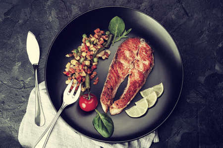Fried salmon fishes and vegetables on plate, cooking delicious and healthy, fresh sea food. Cooking background, flat lay. Vintage stylization, retro film filter