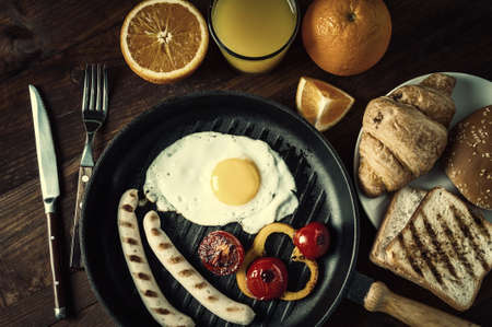 Fried sausage with eggs and vegetables on pan. Delicious breakfast with orange juise and growing on wooden rustic boards, food background. Vintage stylization, retro film filter