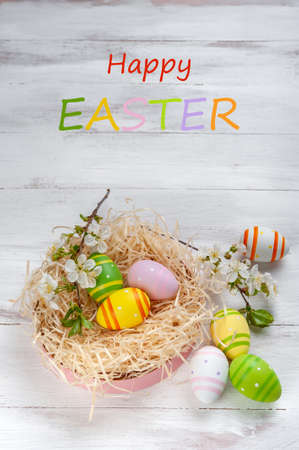 """Easter colorful eggs on wooden backdrop, holiday background for your decoration. Egg hunt, """"Happy Easter"""" lettering"""